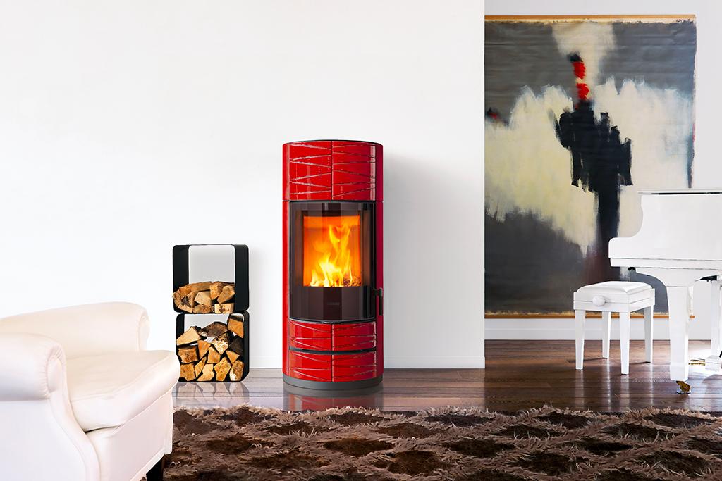 La stufa a legna ROUND M di Piazzetta, cattura tutte le attenzioni grazie al suo colore audace Rosso Lava e ai raffinati pannelli in Maiolica decorati.